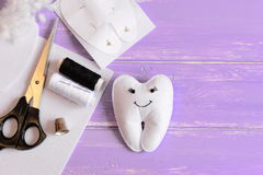 Felt tooth fairy doll, paper template, felt piece in a tooth shape, scissors, thread on wooden background with copy space for text Stock Photo