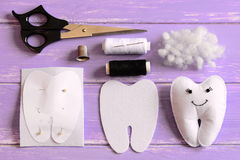 Felt tooth fairy, paper template, felt piece in a shape of a tooth, scissors, thread, needle, filler, thimble on table Royalty Free Stock Photo