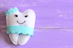 Felt tooth fairy pillow isolated on wooden background with copy space for text. Handmade children`s felt tooth fairy pillow Royalty Free Stock Images