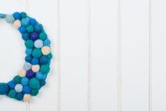 Felted在木背景的羊毛项链 现代妇女的五颜六色的蓝色项链 库存图片