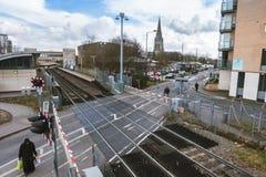 Feltham järnvägsstation med sikt in mot tornet av dendemolerade kyrkan för ` s för St Catherine Arkivfoto