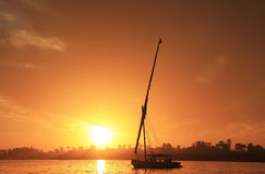 Felucca boat sailing on the Nile river at sunset, Luxor. Egypt Stock Photos