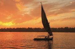 Felucca boat sailing on the Nile river at sunset, Luxor. Egypt Royalty Free Stock Image