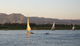 Felucca's on the Nile. Three felucca's on the Nile in Egypt at Luxor showing the Valley of the Kings in the background Royalty Free Stock Images