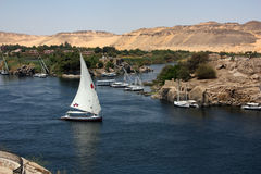 Felucca sailing the Nile. A Felucca (traditional wooden sailing boat) going down the Nile river along Aswan, Egypt stock photography