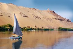 Felucca sailing on Nile river, Egypt. In Background Aga Khan Mausoleum on a island in Nile river stock photo