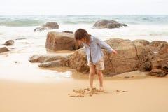 Femårig flicka som spelar på den sandiga stranden av havet royaltyfri fotografi