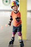 Femårig pojke med hans tumme upp visning att han gillar att åka skridskor för rulle Utrustad pojke som bär en hjälm Utarbeta i en Royaltyfri Foto