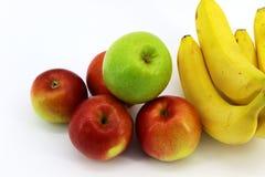Fem äpplen och fyra knäpp som förläggas på en vit bakgrund royaltyfria foton