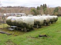 Fem åldriga propangasbehållare i gräs område royaltyfria foton