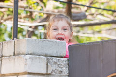 Fem-år flicka som ler den sedda ut bakifrån väggen Arkivfoto