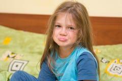 Fem-år flicka som vaknar upp att sitta på sängen och blickarna som är löjliga i ramen Royaltyfria Bilder
