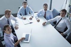 Fem affärspersoner som har ett affärsmöte på tabellen i kontoret som ser kameran Arkivfoto