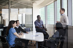 Fem affärspersoner som sitter på en konferenstabell och diskuterar under ett affärsmöte Arkivfoto