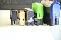 Fem automatiska stämplar för handtag, ark av papper på ett skrivbord arkivbilder