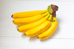 Fem bananer på träbakgrund Royaltyfri Foto