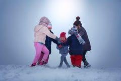 Fem barn har gyckel i snön royaltyfria bilder