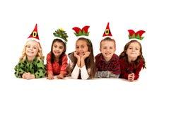 Fem barn i enfaldiga julhattar som ner lägger Royaltyfri Bild