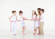 Fem barn i vitkläder drar lite över rep. Royaltyfria Foton