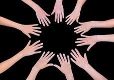 Fem barnhänder som sammanfogar i cirkel ovanför svart bakgrund Royaltyfri Foto