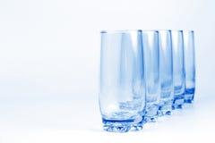 Fem blåa genomskinliga exponeringsglas med ett ljus - blå bakgrund Royaltyfri Fotografi
