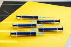 Fem blåa injektionssprutor på en guling och en svart ytbehandlar i rommarna för sol` s arkivbilder