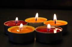 Fem brännande stearinljus mot en mörk bakgrund Arkivbilder