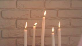 Fem brännande stearinljus mot tegelstenväggen