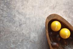 Fem bruna chokladeaster ägg och två gula stearinljus i träplatta Royaltyfri Foto