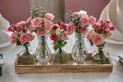 Fem buketter av rosor på en festlig brölloptabell i restauren Fotografering för Bildbyråer