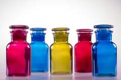 Fem färgade flaskor och deras glass stordia Arkivfoto