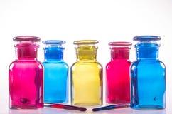 Fem färgade flaskor och två borstar Royaltyfri Fotografi