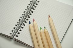 Fem färgade träblyertspennor på bakgrunden av ett tomt ark av notepaden fotografering för bildbyråer