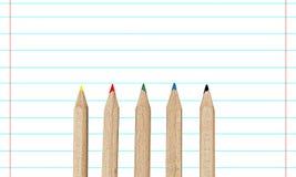 Fem färgblyertspennor på en linje papper Royaltyfri Fotografi