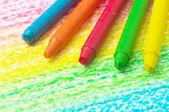 Fem färgpennor och teckning av regnbågen. royaltyfria foton