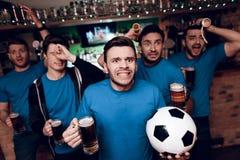 Fem fotbollfans som dricker ledset öl att deras lag lossar på sportstången royaltyfria bilder