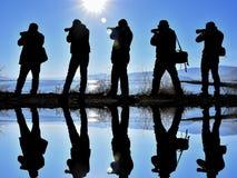 Fem fotografer bredvid en sjö Arkivbild
