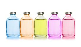 Fem färgade flaskor med nödvändiga oljor Arkivfoton