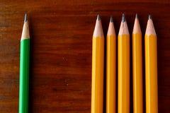Fem gula blyertspennor och en grön blyertspenna Royaltyfria Foton