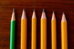 Fem gula blyertspennor och en grön blyertspenna Royaltyfri Fotografi