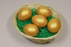 Fem guld- ägg i korg Fotografering för Bildbyråer
