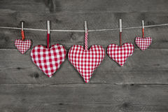 Fem handgjorda röda rutiga hjärtor på trägrå bakgrund Royaltyfri Fotografi