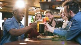 Fem hipstervänner som klirrar exponeringsglas med öl och coctailar i stången, bar lager videofilmer