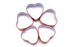 Fem hjärta formade metallbehållare som är ordnade i en kronbladmodell Royaltyfria Bilder