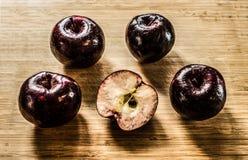 Fem karmosinröda äpplen lägger på en träskärbräda arkivfoton