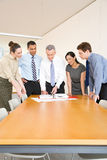 Fem kollegor runt om ett skrivbord royaltyfria bilder