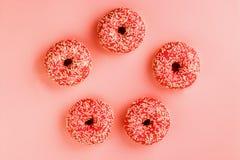 Fem koralldonuts Donuts med isläggning på rosa bakgrund arkivfoto