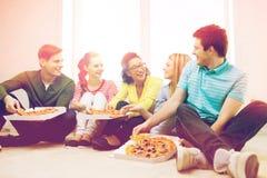 Fem le tonåringar som hemma äter pizza Fotografering för Bildbyråer