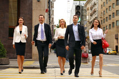 Fem lyckade affärspersoner som korsar gatan i staden Arkivfoto