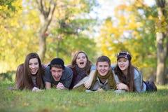 Fem lyckliga tonår utomhus Arkivbilder